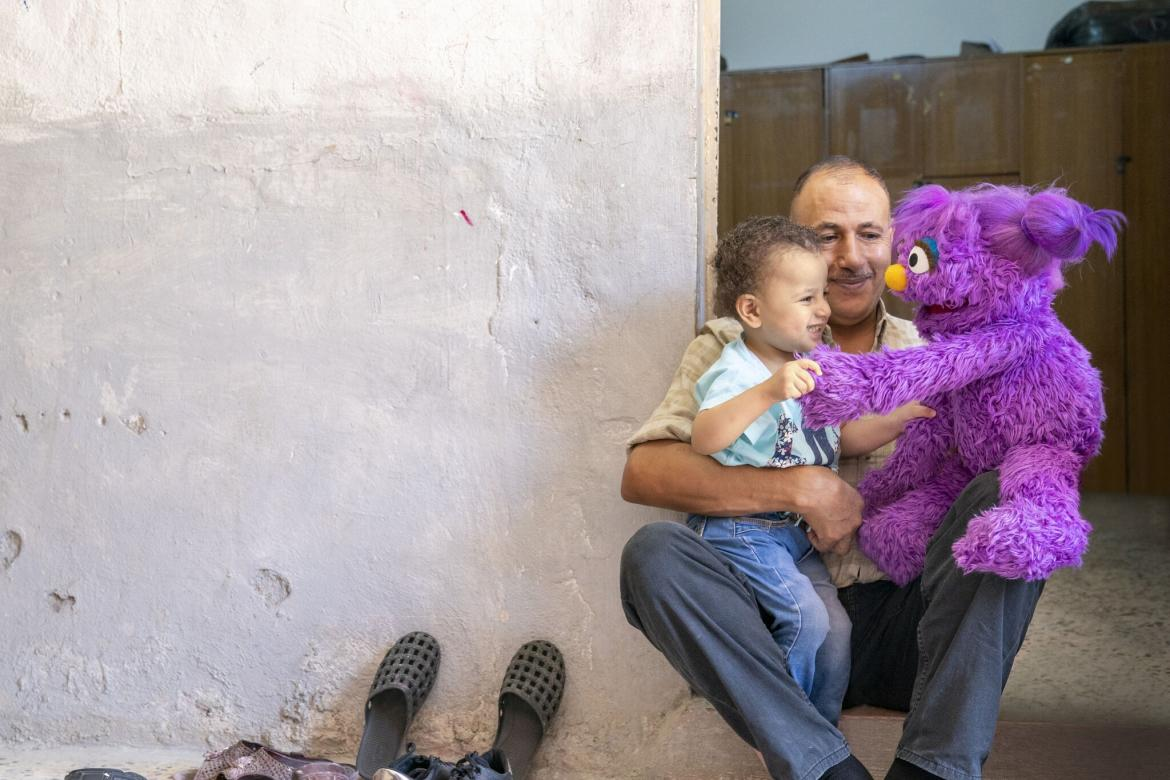 Basma, a Muppet character from Ahlan Simsim, meets a young child and caregiver in Amman, Jordan.