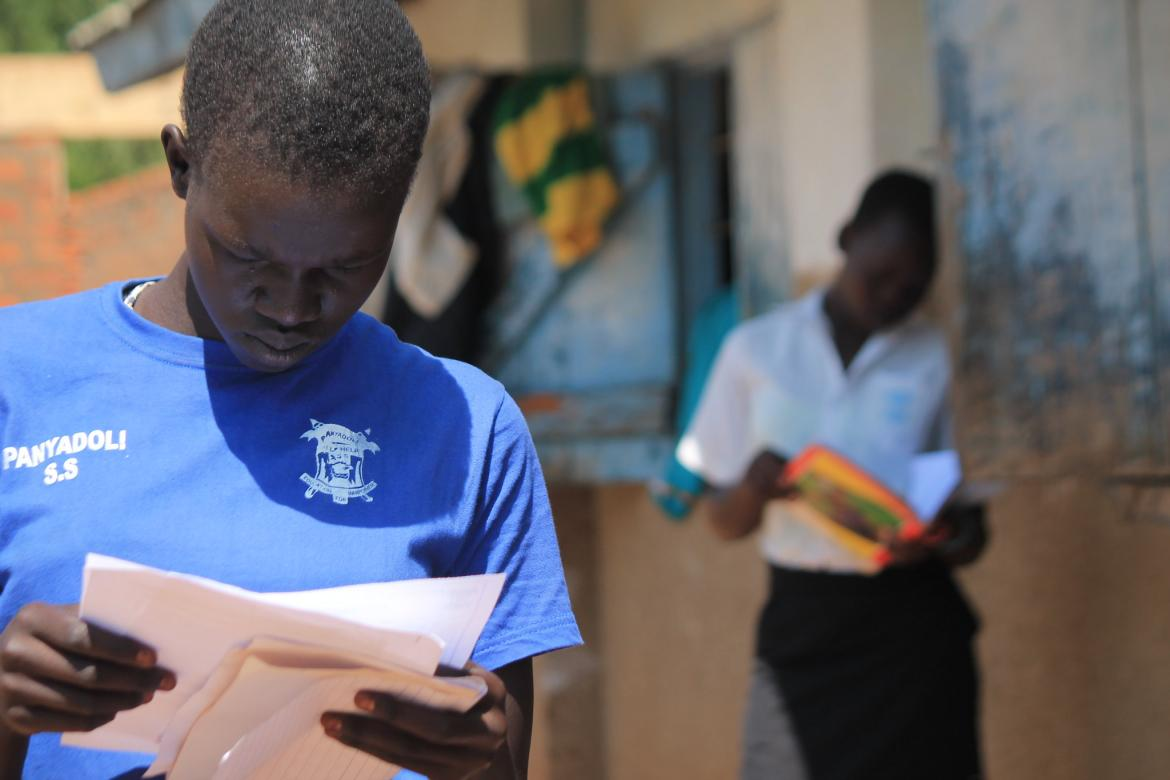 Students look at their report cards. Uganda