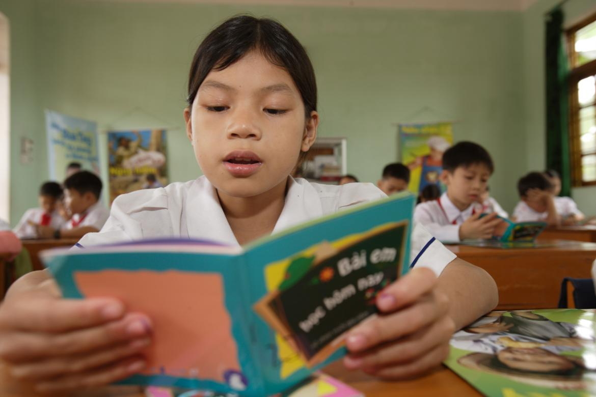 A student reading a book in her classroom. Credit: UNICEF/Jim Holmes