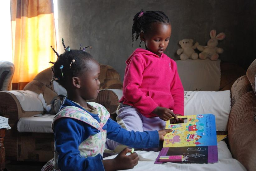 Two little girls read at home in Kenya. Credit: Copyright: Barbara Lee