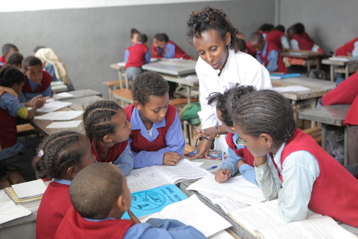 A teacher helping a group of students during a class at Hidassie School in Addis Ababa, Ethiopia. November 2013.
