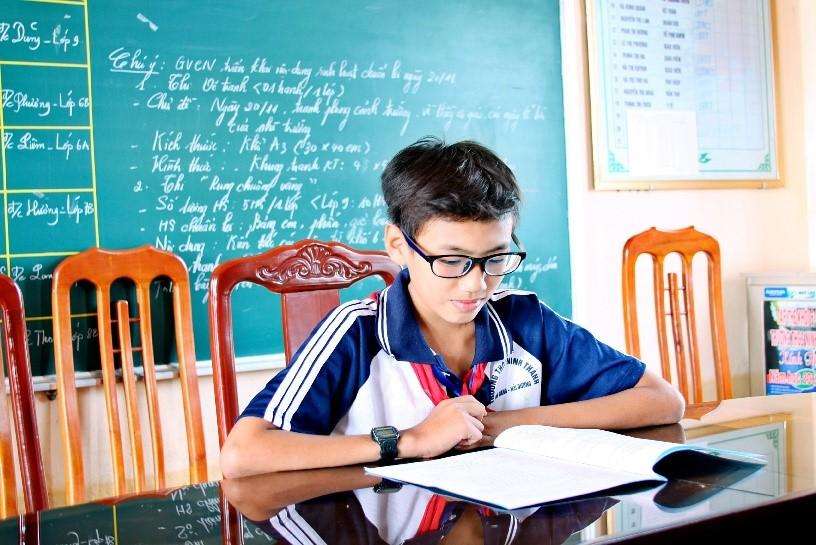 Manh Nghia is wearing the glasses provided as part of the Fred Hollows Foundation Vietnam Child Eye Care project