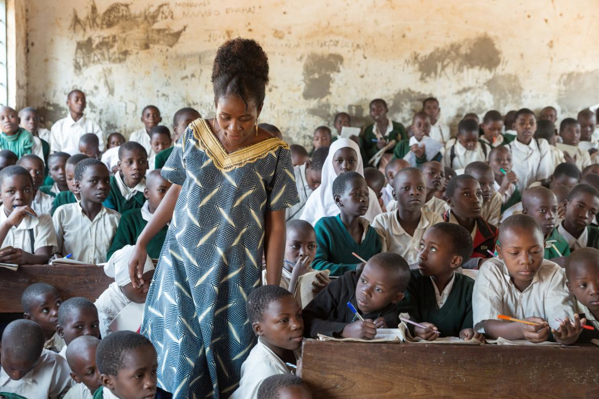 The principal of the Kivukoni Primary School wades through students in the Standard 4 classroom. Overcrowded classrooms and high pupil-teacher ratios are impacting teaching and learning outcomes in many primary schools in Tanzania. Credit: GPE/Kelley Lynch