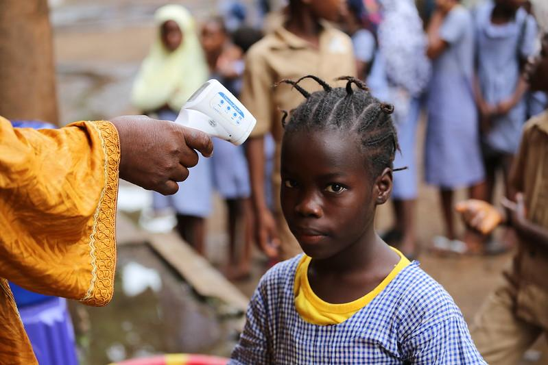A young girl having her temperature checked before entering her classroom at the École du Centre in Conakry, Guinea.
