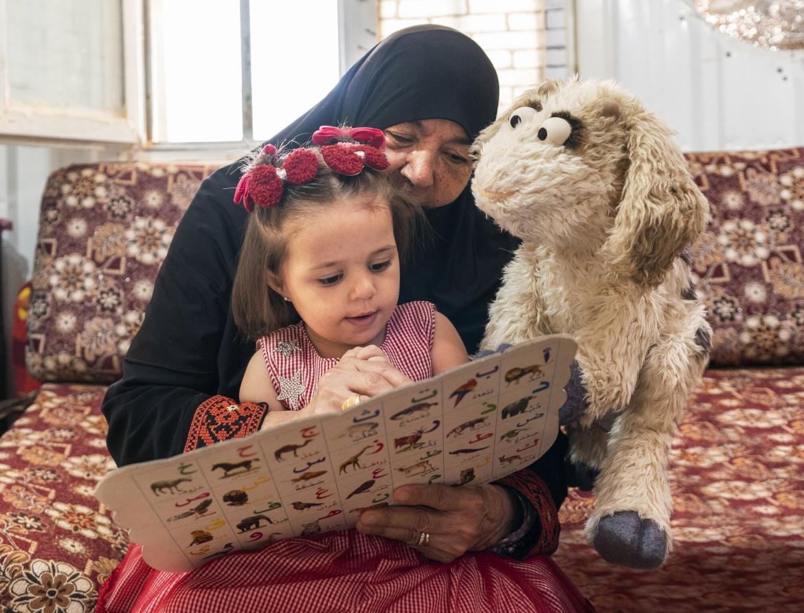 Ma'zooza, a Muppet character from Ahlan Simsim, reads along with a child and caregiver in Mafraq, Jordan.