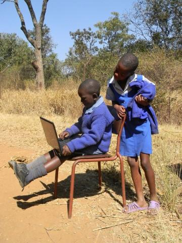 Two primary school children use a laptop outside their home as more children in Africa now have access to computers.