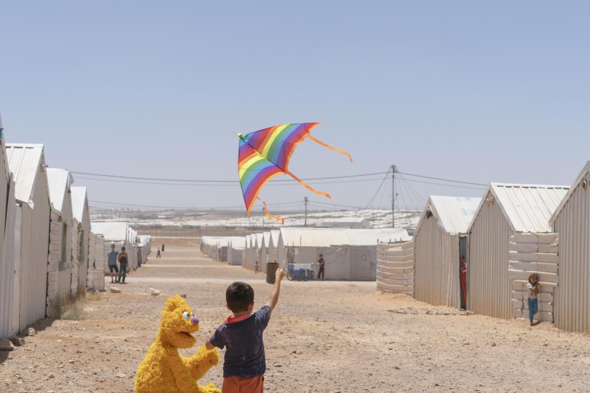 Jad, a Muppet from Ahlan Simsim, flies a kite with a new friend in Azraq camp, Jordan.