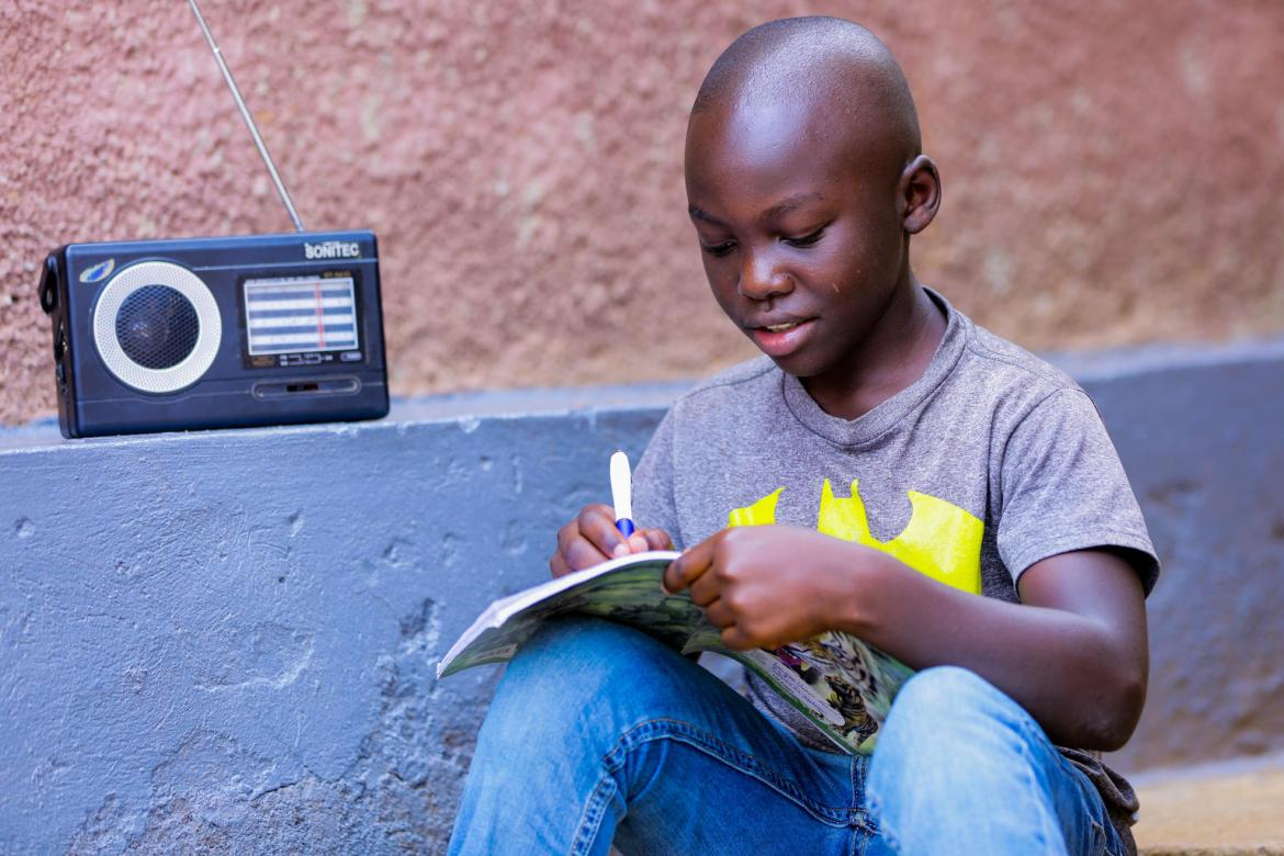 Igihozo Kevin, 11, studies at home due to coronavirus-related school closures, listening to his Primary 5 lessons on the radio every day.