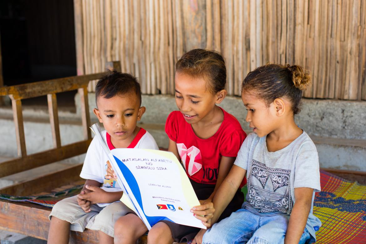 A girl reads as children look on in Timor-Leste. This book is part of a series of audio-visual and printed material produced by the Ministry of Education and UNICEF to help children continue learning during ongoing school closures. Television programs, radio programs and e-books, as well as a book for parents to explain COVID-19 to children with neurodevelopmental needs, are available on the Learning Passport platform developed by Microsoft, UNICEF and the University of Cambridge. Credit: © UNICEF/UNI320753