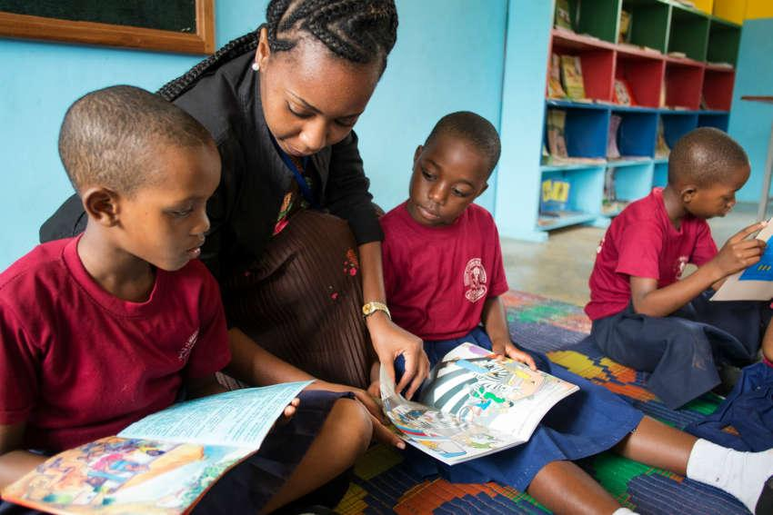 A teacher supporting children's independent reading in Tanzania.