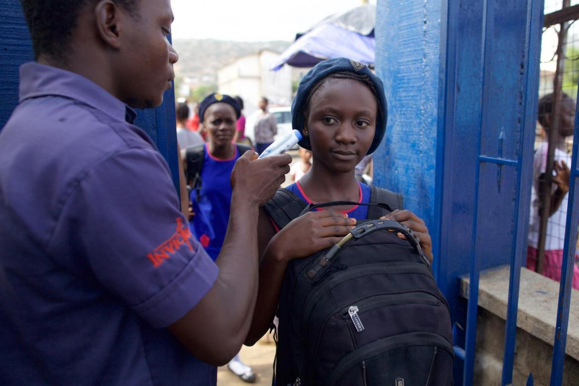 A young man takes a girl's temperature at the entrance to St. Joseph's Secondary School in Freetown, Sierra Leone © UNICEF/UNI182842/Irwin