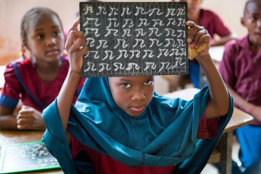 Image: A young girl holds up her chalkboard. First grade classroom at Ecole Madina III, Niamey, Niger. April 2017. Credit: GPE/Kelley Lynch