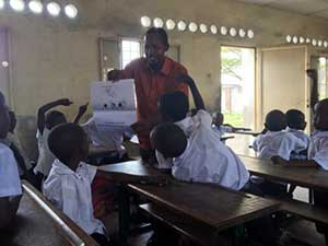 A teacher reading out loud to his Grade 2 students at the Kinshasa school in DRC