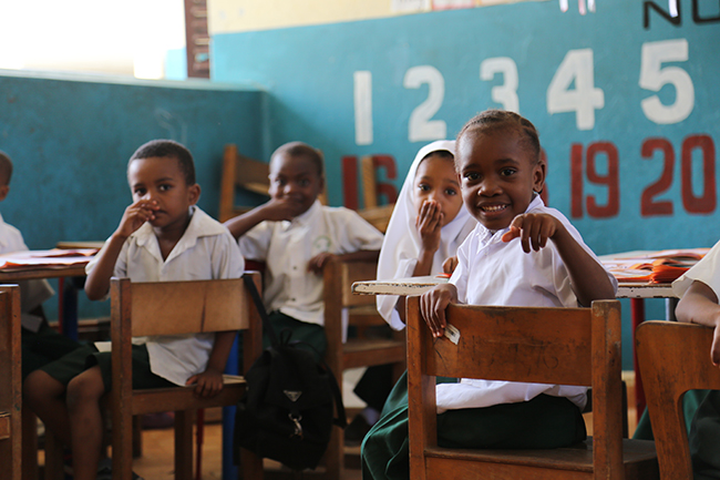 Children in a pre-primary classroom at Kisiwandui primary school in Zanzibar learn new words through looking at images in their textbooks and repeating them after their teacher. Credit: GPE/Chantal Rigaud