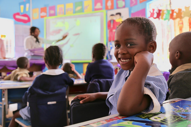 A school kid smiles at the camera in a classroom in Zimbabwe. Credit: GPE/ Carine Durand