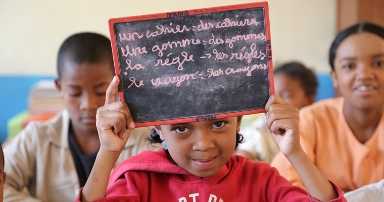 A school girl holds a slate in Madagascar. Credit: GPE/Carine Durand