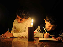 This photo is of refugee children reading and writing in Gaza. Due to the blockade, Gaza suffers from severe fuel and electricity shortages resulting in 12-hour-blackouts each day. The children, undeterred, read by candlelight. Credit: Shareef Sarhan, United States