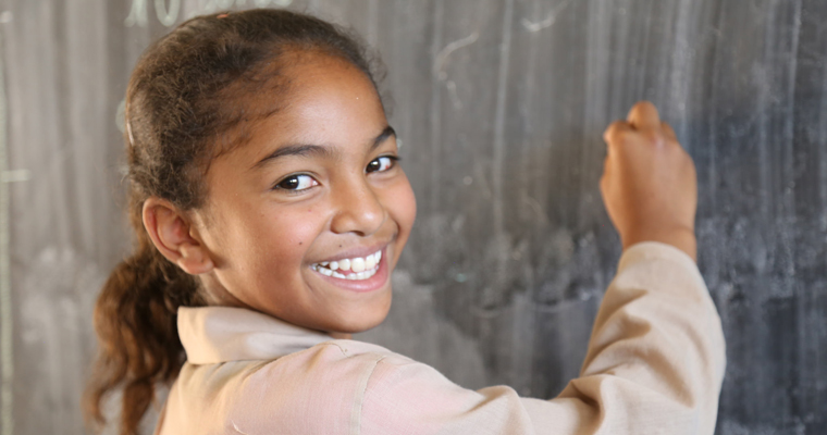 A girl writes on the blackboard in a school in Madagascar. Credit: GPE/Carine Durand