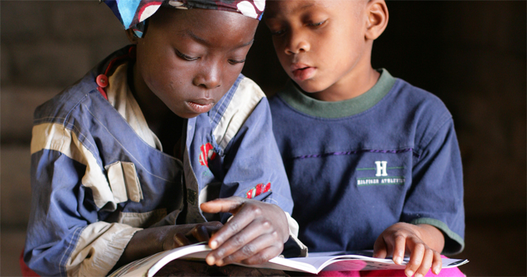 Two school kids read a book in Mozambique. Credit: UNICEF/Giacomo Pirozzi