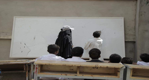 A teacher in Nokhom, in the capital Sana'a, is using a school yard to give classes to children who have been displaced with their entire families to the classrooms within the same school.