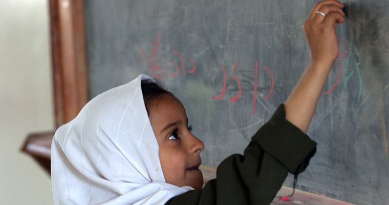 A young girl writing on the blackboard at Attabari Elementary School, Yemen. Credit: UNESCO/Linda Shen