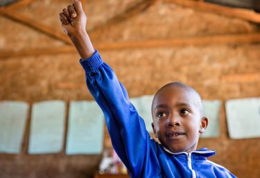 Student in first grade classroom raises his hand. Nyamachaki Primary School, Nyeri County, Kenya. Credit: GPE/Kelley Lynch