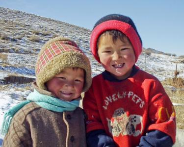 Two small children smile with mountains in the background. Kyrgyz Republic. Credit: World Bank/Nick van Praag