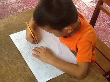 A boy learns to write at his desk, in a pre-primary classrom in Lao PDR. Credit: Mary Young