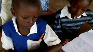 A girl, with pen in pocket, and boy sit at a desk to learn math out of a workbook. Credit: GPE