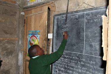 Boy writing answers on chalkboard, Kenya. GPE/Deepa Srikantaiah