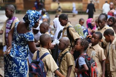 Children lining up to have their temperature taken before entering school in Conakry, Guinea © GPE/ Tabassy Baro
