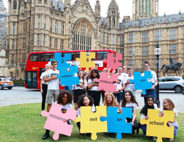 Send my Friend to School campaigners pose with their puzzle pieces in front of the Parliament in London. Credit: SFS